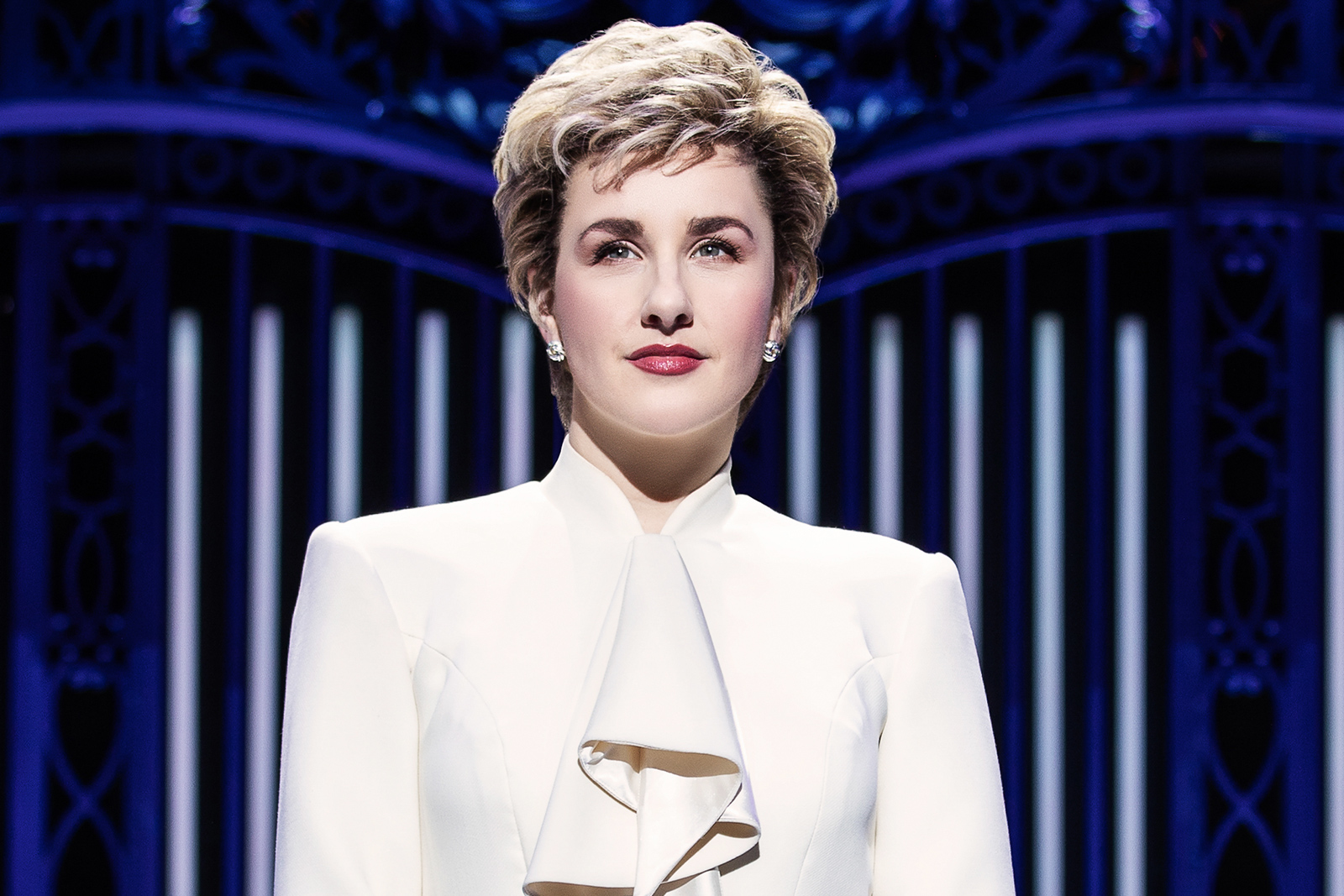 A still from Diana The Musical. A white woman with short cropped hair is staring into the middle distance. She is wearing a cream ruffled shirt and looks composed and contemplative, in front of an ornate backdrop.