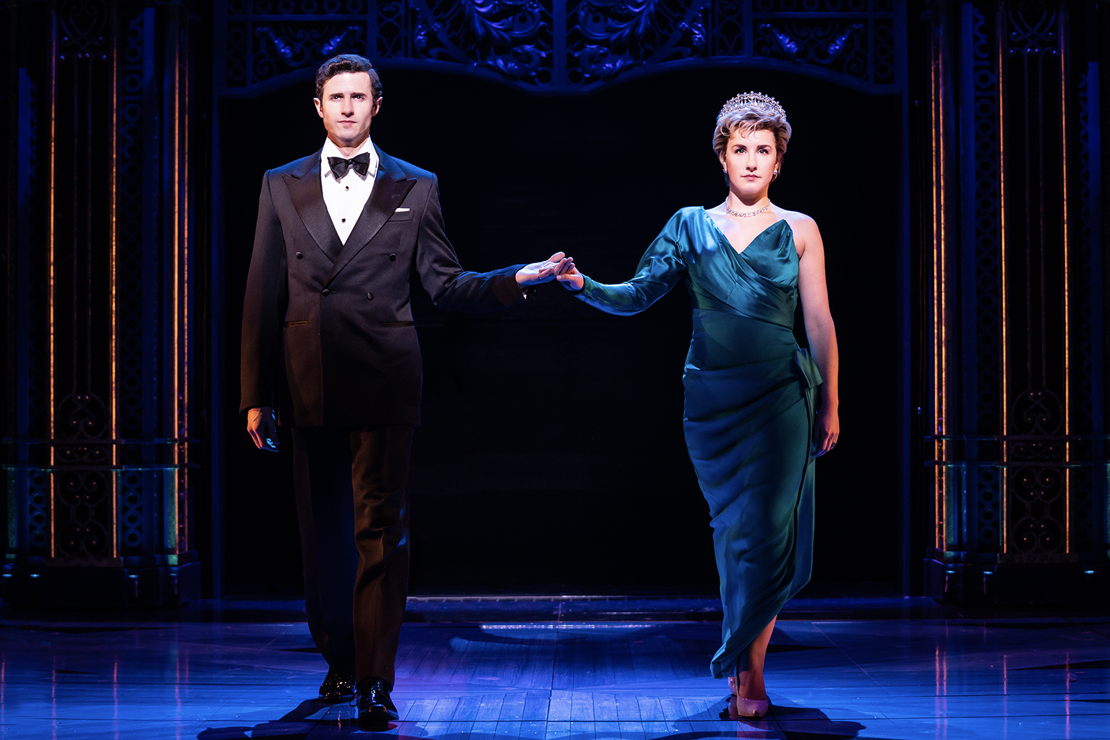 The actors playing Charles and Diana are holding hands and facing the camera. They are dressed in formal attire and have serious facial expressions.